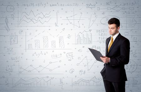 A confident young businessman standing in front of wall with drawn pie charts, graphs, numbers, arrows concept