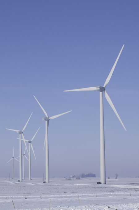 Wind turbines stand above wintry farmland in northern Illinois (roadside view)