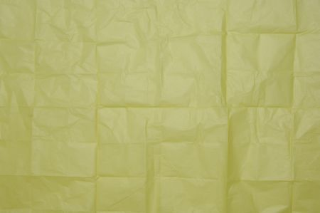 Texture of yellow wrapping paper once folded into squares