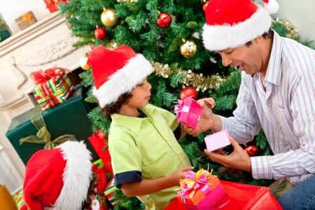 Boy giving a Christmas present to his father