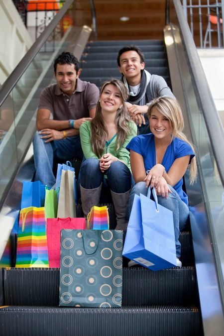 Group of friends on escalator shopping in a mall with some bags