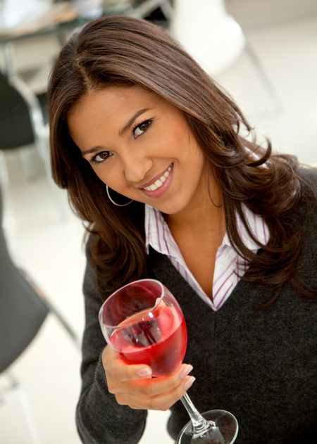 Woman having a glass of ros? wine and smiling