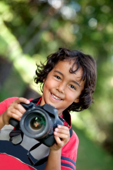 Boy playing with a camera outdoors and smiling