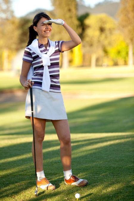 Woman at the course playing golf and smiling
