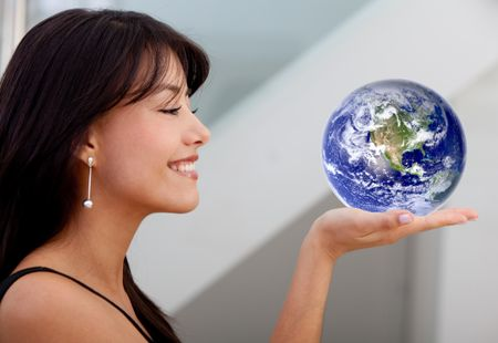 Beautiful business woman smiling and holding globe on her hand