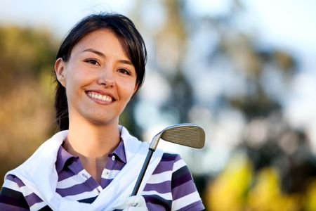 Female golf player outdoors with a club smiling