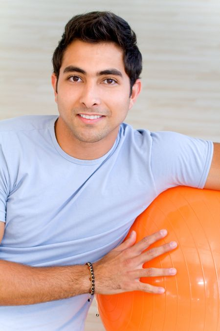 handsome man portrait at the gym smiling leaning on a pilates ball