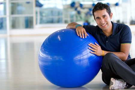 man at the gym leaning on a pilates ball and smiling