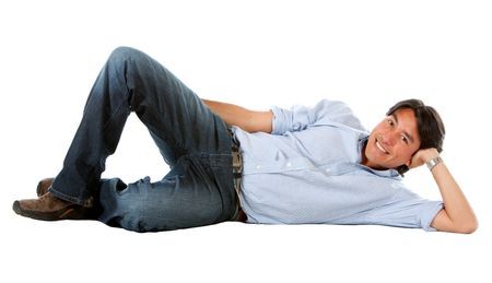 casual man smiling and lying on the floor isolated over a white background