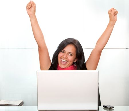 business woman on a laptop full of success with her arms up