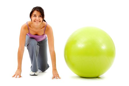fitness woman with a pilates ball - ready to race isolated over a white background