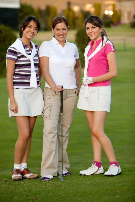 Happy group of female golf players outdoors and smiling