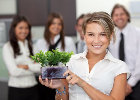 Business woman holding a small tree at the office with a group behind