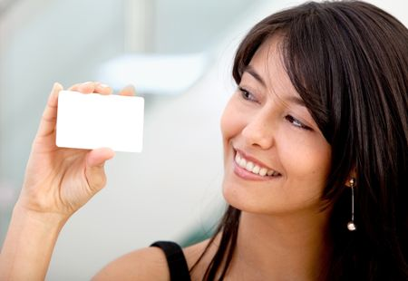 Woman displaying a business card and smiling