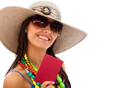 Woman ready to travel wearing a hat and holding her passport - isolated