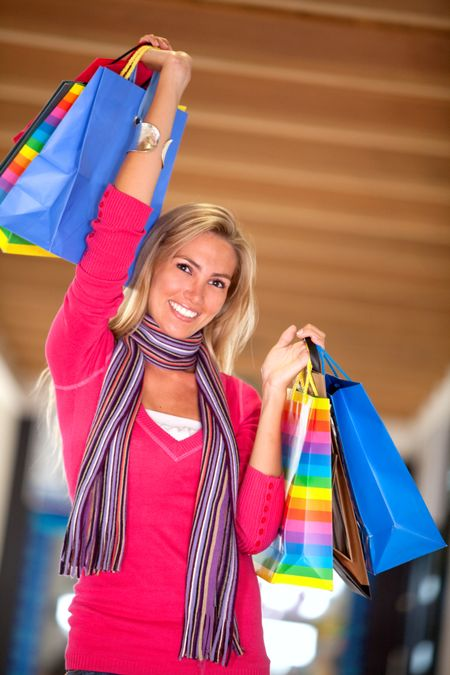 happy woman smiling with shopping bags in a mall