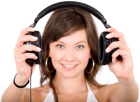 music for your ears - girl holding headphones in front of the camera over a white background