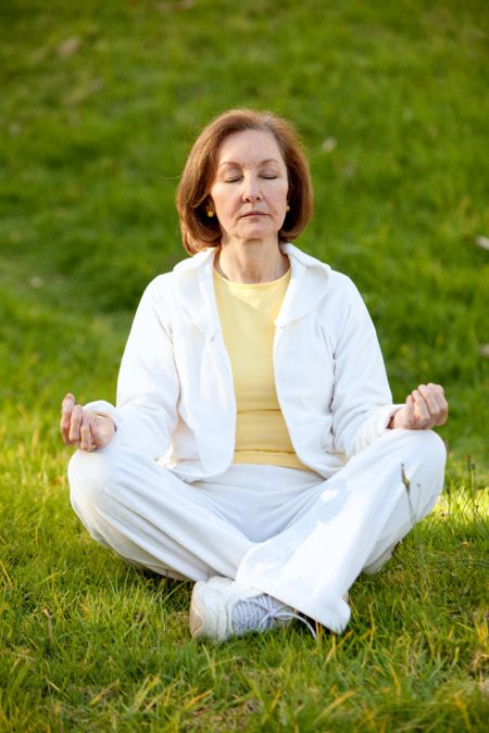 Woman with her eyes closed practicing yoga outdoors
