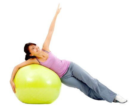 Fit woman exercising with a pilates ball - isolated over a white background