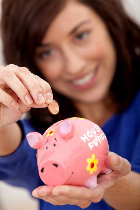 Woman putting a coin into a piggybank for the house budget