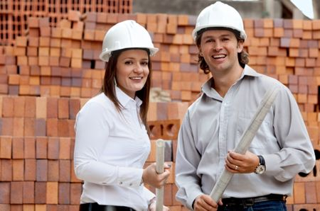 Engineers at a construction site holding blueprints and smiling