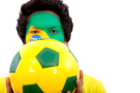 Portrait of a man with the brazilian flag painted on his face holding a soccer ball isolated over white