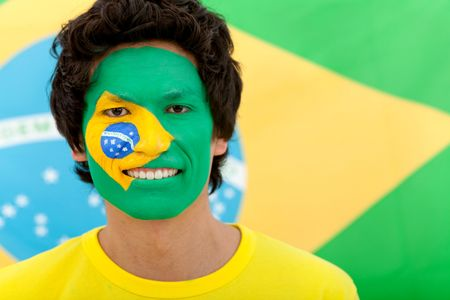 Portrait of a man with the brazilian flag painted on his face