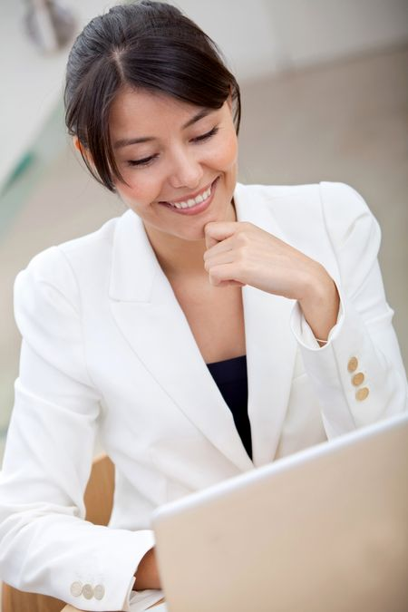 business woman looking happy on a laptop in her office