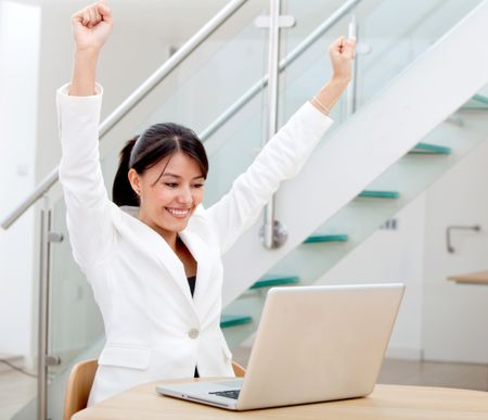 Successful business woman looking happy on a laptop in her office