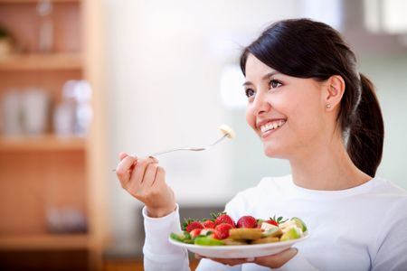 casual woman smiling and having fruit for breakfast