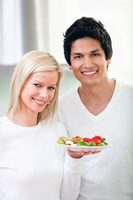 Healthy eating couple smiling and holding a dish of fruit