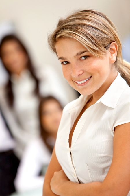 Business woman smiling with her team behind her at the office