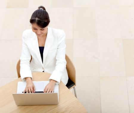 Business woman working on a laptop at the office and smiling