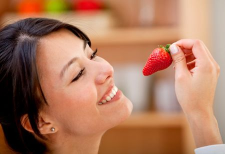 Beautiful woman about to eat a strawberry and smiling