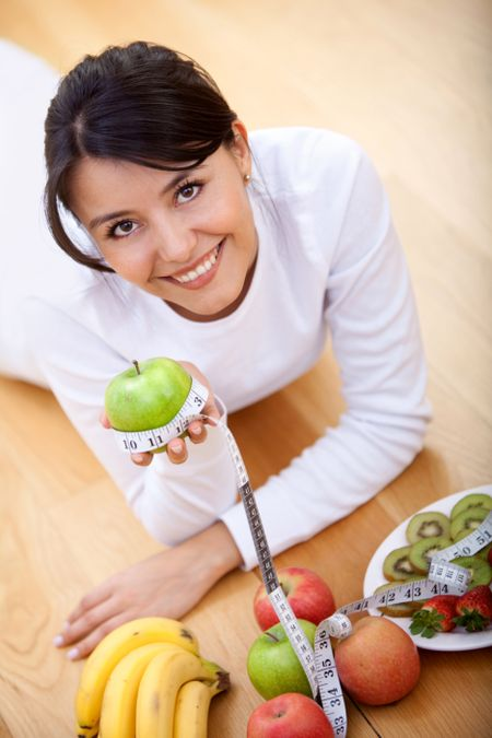 Healthy eating woman lying on the floor with fruits