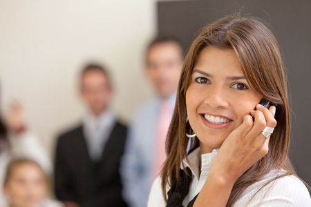 Business woman smiling and talking on the phone at the office