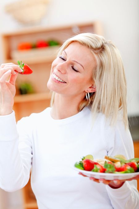 Healthy eating woman with a fruit salad and smiling