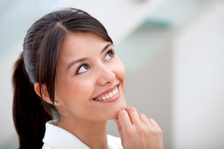Thoughtful business woman at the office and smiling