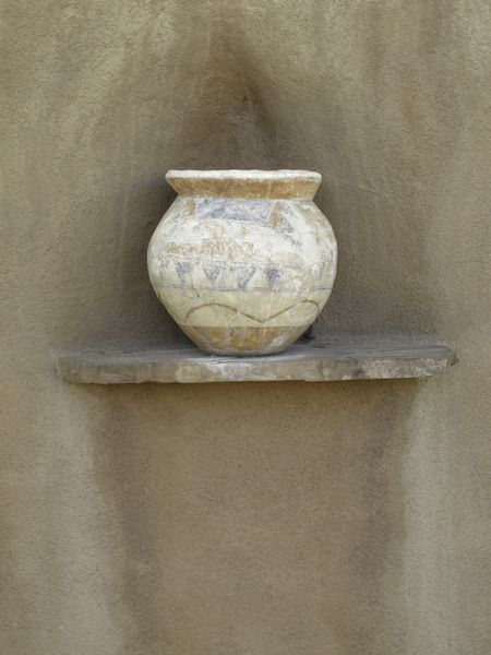 Ceramic pot with faded paint on ledge of exterior adobe wall