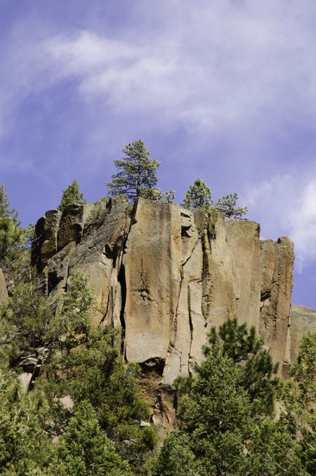 Cliff with pines under partly cloudy sky high in Jemez Mountains in northern New Mexico