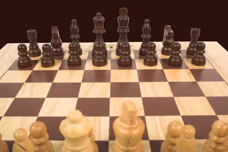 chess set  focusing on black pieces with white ones at the bottom (blurred)