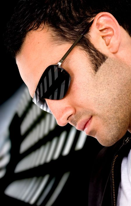 fashion male portrait wearing sunglasses isolated over a dark background
