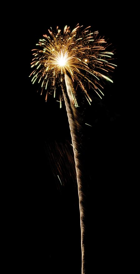 Flowerlike bloom of fireworks with white-hot core and long rocket trail