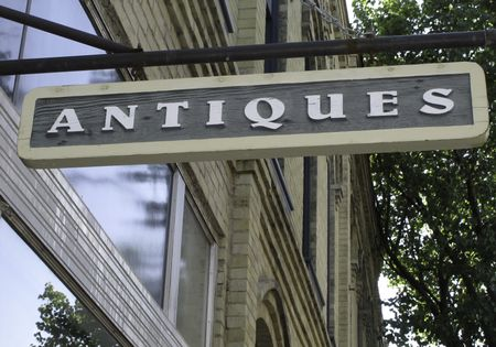 Simple sign hanging outside old brick building with antiques shop