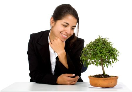 business girl with a tree on her desk smiling over a white background