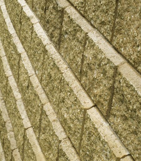 Symmetry of outdoor retaining wall with beveled manufactured-stone veneer