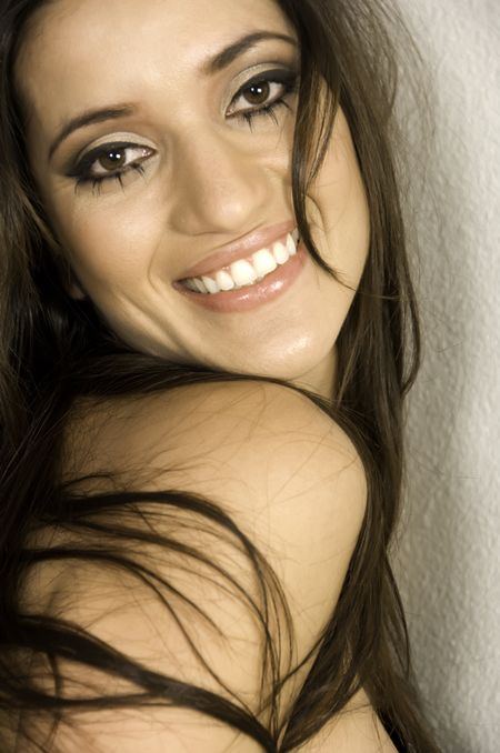 Close-up of young Caucasian brunette with long hair by textured wall, chin on shoulder, head tilted, smiling at the camera