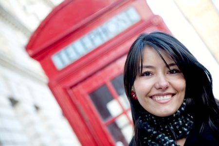 Woman smiling outside a telephone booth in London