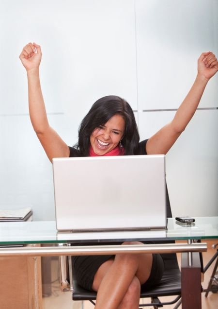 Successful business woman working on a laptop at the office looking excited