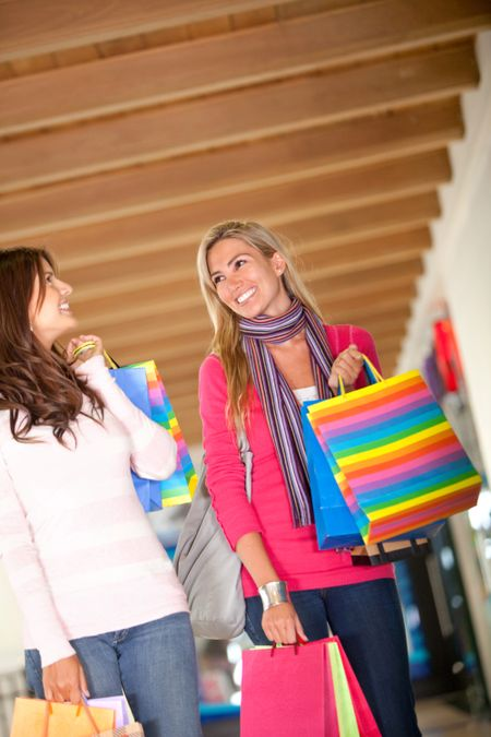 Female friends holding bags at a shopping center and smiling